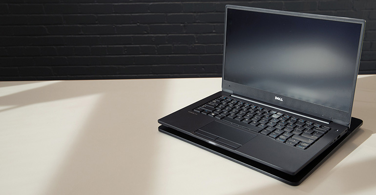 Dell laptop sitting on a WiTricity magnetic-resonance wireless-charging pad.